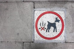 Looking down from above onto a stone pavement with a warning sign reminding dog owners to clean up after their dog does a poo on the city streets of London