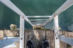 Looking down from the edge of a dock showing black shoes a gray wheathered  ladder, rustic wood floor looking down into the green still water and barnacles.