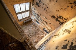 Looking Down Into a Small Room in an Abandoned Building Covered in Debris and Graffiti