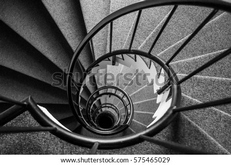 Looking down narrow spiral staircase forming a dramatic pattern #575465029