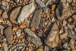 Looking down on a dry part of the riverbed that has several kinds of colorful rocks and stones with little pebbles mixed in closeup backgrounds and textures
