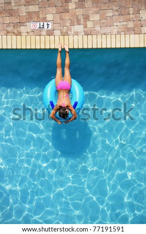Looking down on a girl suntanning in a swimming poo on a pool float / pool ring, room for your text