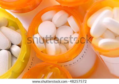 Looking down on a group of open prescription bottles with assorted pills closeup horizontal composition shallow depth of field