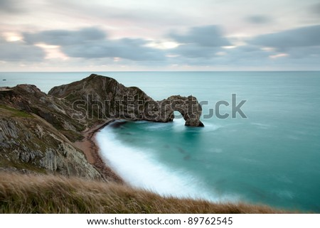 Looking down on Durdle Door in the Jurassic Coast in Dorset, UK.  Taken 30 minutes before sunrise so the clouds have a pre-dawn glow.