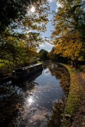 looking down on the canal with the autumn colours in the trees and the still water of the historical canals of Dudley with a canal boat docked on the side