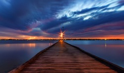 Looking down Pier at colourful sunset and twinkly lights