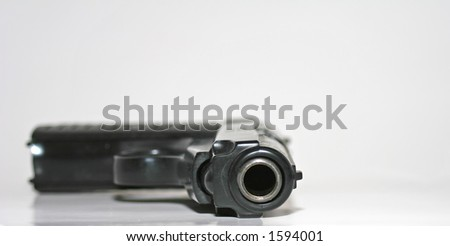 Looking down the barrel of a semi automatic handgun with only the end of the barrel in focus