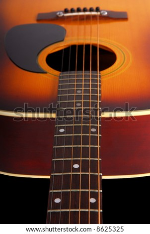 Looking down the neck of acoustic guitar with shallow focus
