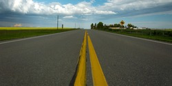 Looking down the yellow solid center line of a rural highway with a storm in the distance