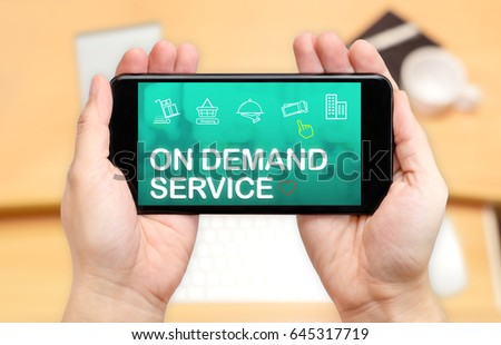 Looking down to see two hand holding mobile phone with On demand service word on screen and blur desk office background,Online shopping concept #645317719