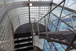 Looking downwards in an open stairwell of a modern office building