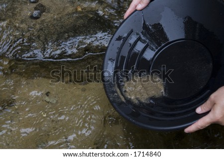 looking for gold in a small stream in northern Michigan by Mackinaw city black pan with sand and gravel in the pan