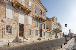 Looking for quiet routes between Cyclades architecture of neoclassic stonewall houses empty cobblestone street sun calm sea blue sky hospitable people at Ermoupoli city Syros island destination Greece