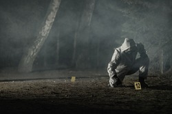 Looking For Traces and Crime Evidence Markers Placing by Forensic Officer in Hazmat Suit and Gloves. Dark Foggy Forest. Crime Scene Theme Concept.