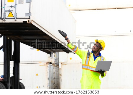 Looking forword. Foreman using laptop computer in the port of loading goods. Foreman showing thumbs up on Forklifts in the Industrial Container Cargo freight ship. ストックフォト ©