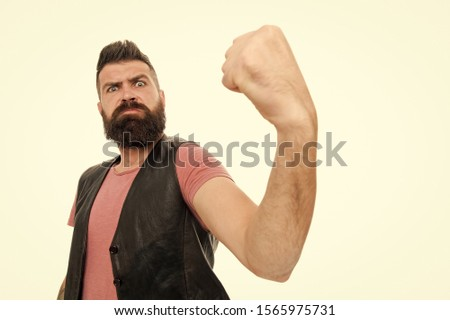 Looking frighteningly as a muscular man. Bearded muscular man shaking fist. Brutal hipster flexing his arm with muscular power. Building muscular strength and flexibility.