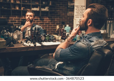 Looking good. Side view of handsome young bearded man looking at his reflection in the mirror and keeping hand on chin while sitting in chair at barbershop