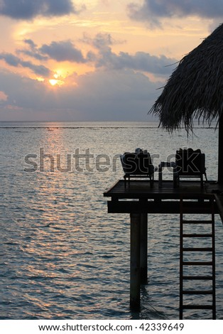 Looking on sunset in Maldives from terrace of watervilla - stock photo