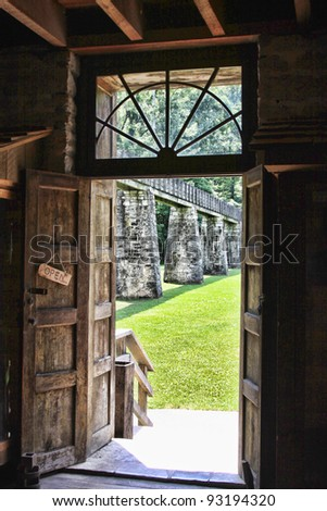 looking out door at water trough at a grist mill at Spring Mill State Park - stock photo