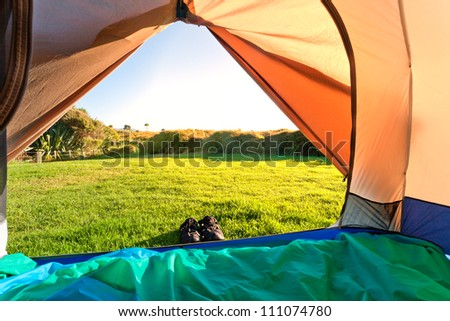 Looking out of open tent door upon green meadow and forest in morning sunshine
