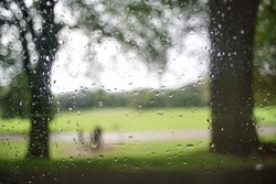 Looking out of the window from a car, typical fall mood, raindrops on the surface with a park background