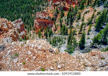 Looking over a cliff down into a valley with green trees and red sandstone formations. #1091953880