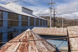 Looking over tin rooftops to cloudy skies of an abandoned factory complex in the deep south