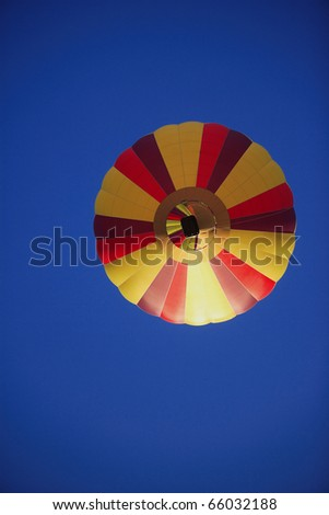 Looking straight up at a hot air balloon in flight.  a colorful balloon is floating in front of a deep blue sky.