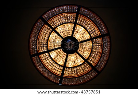 Looking straight up at a lit chandelier