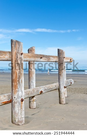 Looking through a wood post fence by the ocean. Rough texture tree trunks form a barrier in the sand. Person running along the shore in blurred background.