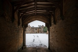 Looking through ancient gatehouse to view of abandoned old derelict run down eerie Manor House boarded up in dark creepy winter snow scene