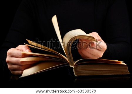 Looking through book with motion blur on black background