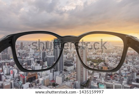 Looking through eyeglasses to city sunset view, focused on lens with blurry background Foto d'archivio ©