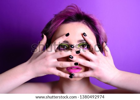 Looking through fingers. Sexy girl with short hair. Portrait of a woman with bright colored hair, all shades of purple. Beautiful lips and makeup. . Professional coloring. professional makeup.