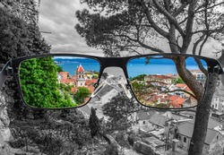 Looking through glasses to colorful view of pine tree,  old city center with red rooftops and blue see surrounded by black and white background. Different world perception. Optimism, hopefulness.