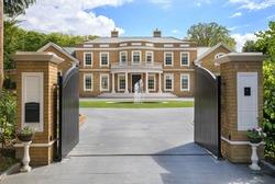 Looking through grand entrance gates to an elegant modern mansion