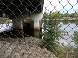 looking through hole in fence at underside of freeway bridge and river
