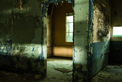 Looking through open doorway in an abandoned factory with peeling paint in a depressed urban area