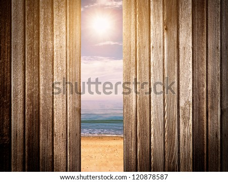 Looking through wooden fence at beach