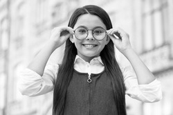 Looking to future. Happy kid fix eyeglasses outdoors. Eye sight development. Child vision. Back to school eye sight test. Pediatric ophthalmology. Primary education. Health and care.