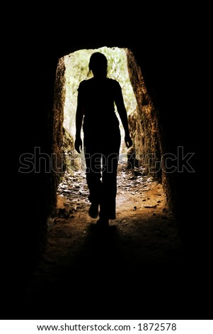 Looking towards the entrance of a cave with a woman walking forwards