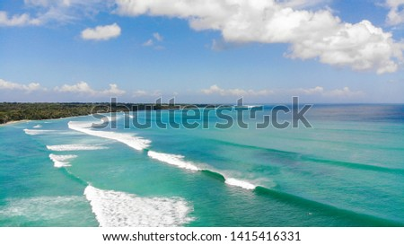 Looking towards the world famous surfers wave G-Land from above. Waves roll into shore below in shallow tropical waters. The national park rainforests boarder the coast #1415416331