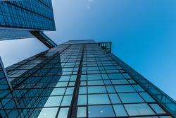 Looking up a tall glass and steel high-rise building