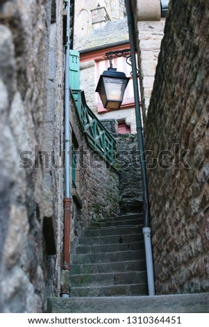 Looking up alleyway beautiful lantern hanging old fashion vintage Mont Saint-Michel france normandy french style antique stairway