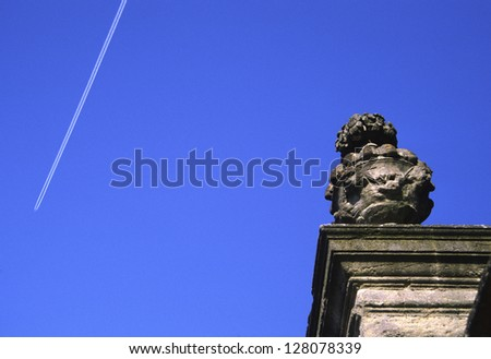 Looking up at a jet trail against blue sky & Carved Urn Detail on Oxford Botanical Garden wall, Oxford, UK