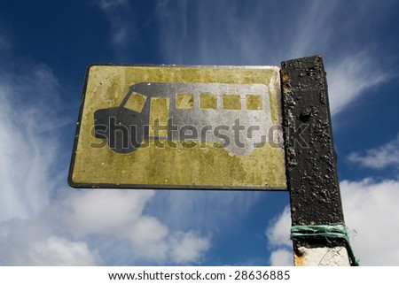 Looking up at a yellow bus stop sign against a blue sky