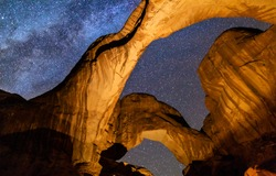 Looking up at Iconic Double Arch illuminated against a star-filled Milky Way in Arches National Park in Moab, Utah.