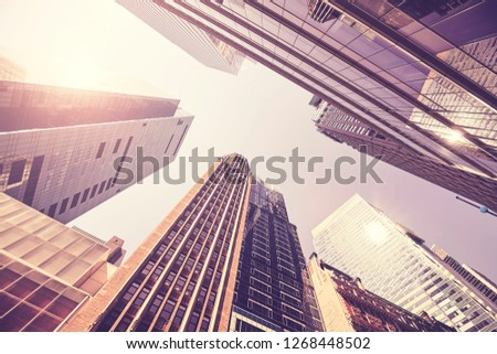 Looking up at Manhattan buildings at sunset, color toned picture, New York City, USA.