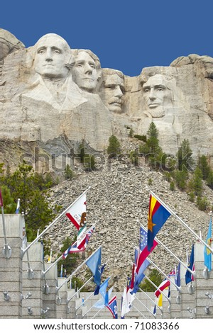Looking up at Mount Rushmore with state flags at the base