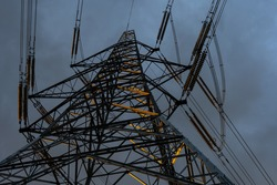 Looking up at sunlit electricity pylon with moody sky at dusk before a storm